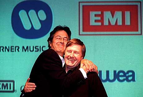 Roger Ames (venstre) var utpekt til sjef for det fusjonerte Time Warner EMI-selskapet med navnet Warner EMI Music. Her gir han Ken Berry en fusjonsklem. Berry var tiltenkt jobben som Ames høyre hånd. Foto: Alastair Grant AP / Scanpix.