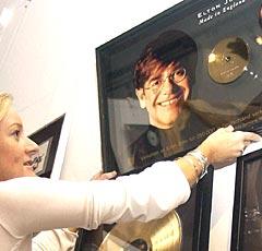 Sandie Maylor hos Sotheby's retter på en av de mange Elton John-gullplatene som ble auksjonert bort. Foto: AFP / Martyn Hayhow.