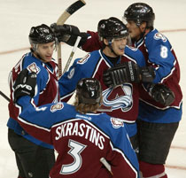 Colorado Avalanche center Joe Sakic, back left, celebrates his goal with linemates Paul Kariya, back center, Teemu Selanne (8) of Finland and Karlis Skrastins