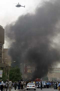 Eit amerikansk helikopter flyg over eksplosjonsstaden i sentrum av Bagdad. (Foto: Ramzi Haidar/AFP/Scanpix)