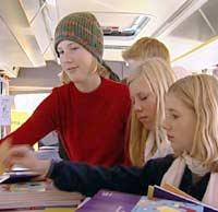 Ungdommer forsyner seg av brosjyrer i bussen.