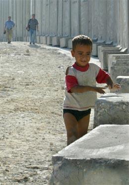 En palestinsk gutt leker ved muren ved landsbyen Sawahreh nær Jerusalem. (Foto: Reuters/Scanpix)