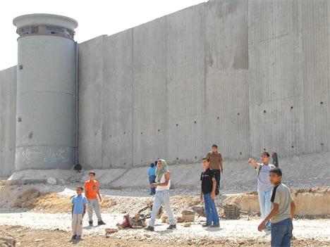 Palestinske barn leker ved muren nær Qalqilya på Vestbredden. (Foto: AP/Scanpix)