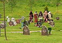 Kvinnene står litt unna under begravelseseremonien. Foto: NRK