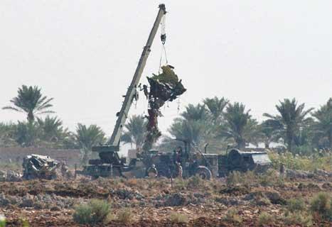 En kran heiser opp restene av det amerikanske helikopteret som ble skutt ned i Irak sist søndag. 15 amerikanske soldatar ble drept. (AP-foto)