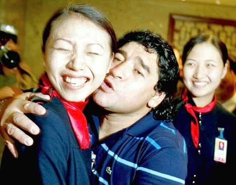 Maradona kysser en flyplassansatt i Beijing, mens en kollega ser på i skrekkblandet fryd. (Foto: Reuters/Scanpix)
