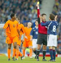 Terje Hauge ga gult kort til Skottlands Christian Dailly for å ha trukket Patrick Kluivert i trøya. (Foto: AFP/Scanpix)