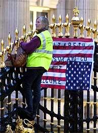 Til tross for de 14.000 politifolkene har det lykkes en demonstrant å klarte helt til topps i porten på Buckingham Palace (Scanpix/AP)