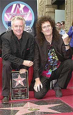 Det er trommis Roger Taylor som synger låta med Nelson Mandela. Her sammen med gitarist Brian May i det Queen registreres på Hollywood Walk of Fame. Foto: Nick Ut, AP.