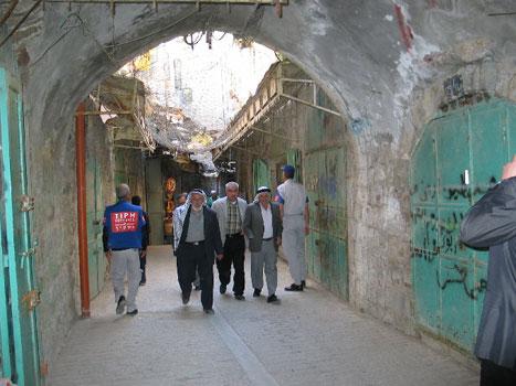 I denne palestinske handlegata i Hebron er neste alle butikker stengt. Jødiske bosetter kaster stein og søppel som er spent over gata til beskyttelse.