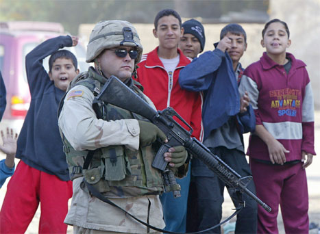 Irakiske barn samler seg rundt en amerikansk soldat som holder vakt etter en bombeeksplosjon i Bagdad i formiddag. (Foto: Reuters-Scanpix)