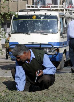 Ein politimann undersøkjer staden der bomba eksploderte. (Foto: AP-Reuters)