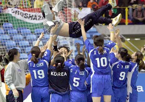 De sør-koreanske spillerne kastet treneren i været etter seieren. (Foto: AP/Scanpix)