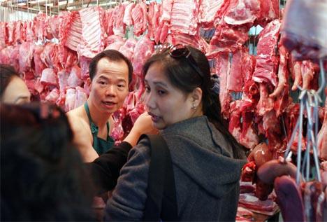 En slakter selger kjøtt på markedet i Hongkong, mens Kina nå innstiller import av kjøtt fra USA. (Foto: AFP/Scanpix)