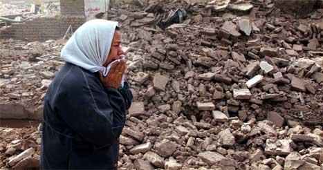 En kvinne gråter foran restene av familiens hus. (Foto: AP-Scanpix)