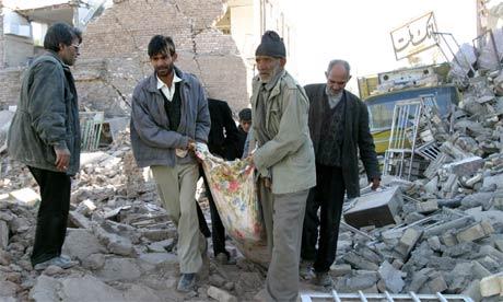Familiemedlemmer bærer deres døde ut fra det som er igjen av et bolighus i den Iranske byen Bam. Foto: Reuters/Raheb Homavandi