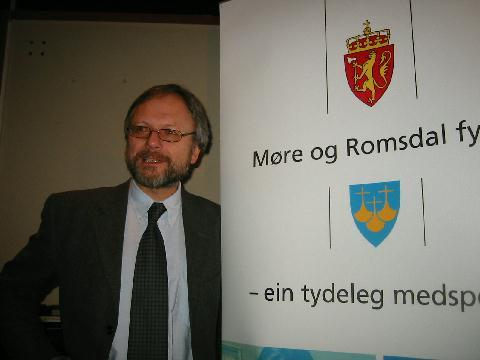 Fylkesdirektør Ottar Brage Guttelvik ved den nye logoen for Møre og Romsdal fylke. Foto: Gunnar Sandvik