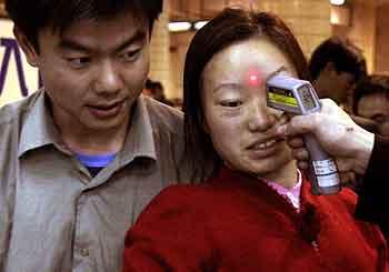 En kinesisk kvinne får målt feberen på en jernbanestasjon i Guangzhou. (Foto: Ng Han Guan, AP)