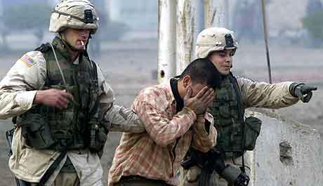 Amerikanske soldater hjelper en gråtende mann bort fra stedet hvor bomben gikk av.  Foto: David  Guttenfelder, AP