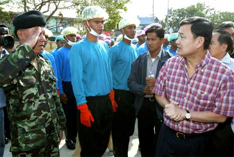 Thailands statsminister Thaksin Shinawatra (t.h.) snakkar med soldatar som er utkommanderte til å slakte kyllingar. (Scanpix/AP-foto)
