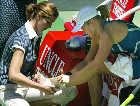 Kim Clijsters får behandling for sin skadde ankel under kampen mot Anastasia Myskina. (Foto: AFP/Scanpix)