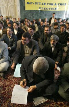 Et medlem av den iranske nasjonalforsamlingen skriver under på sin avskjedsøknad. Foto: AFP/Scanpix