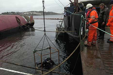 """En dykker kommer opp etter å ha brent hull i skroget på """"Rocknes"""" slik at dykkere kan ta seg inn. (Foto: Scanpix/Marit Hommedal)"""