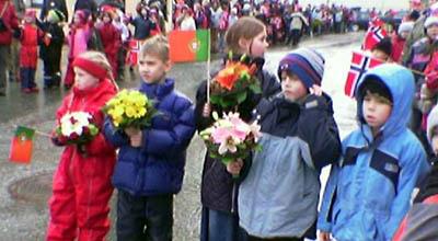 Skulebarn i Ålesund venta med flagg og blomar