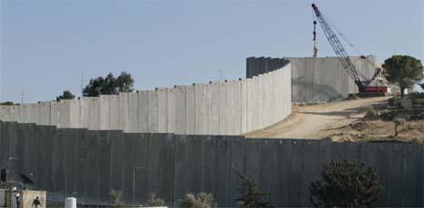 To palestinere beskuer israelernes bygging av den enorme muren på Vestbredden. (Foto: AP/Scanpix)