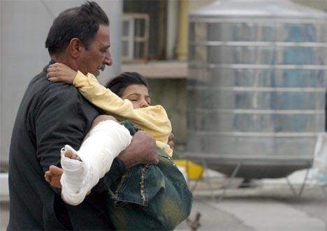 En irakisk far løper med sin sårede sønn til sykehuset. Foto: AFP/Reuters