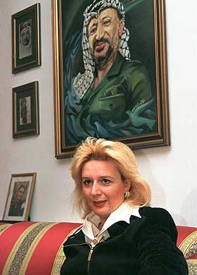 Suha Arafat under et portrett av sin mann, palestinernes president Yasir Arafat. Foto: Adel Hana, AP)