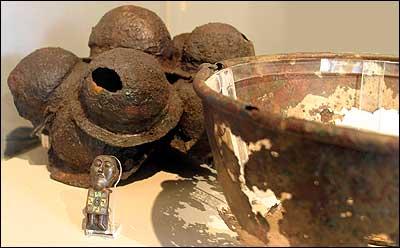 Skjoldbuler frå skjolda som sto langs skipssida, bronsekjele og figur frå kjelen. Utstilt på Bergen Museum. (Foto: Arild Nybø, NRK)