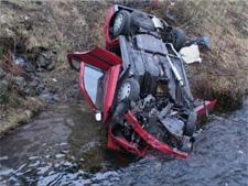 Bilen havnet på taket i Nesttunelven. (Foto: Alrik Velsvik, NRK Hordaland)