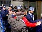 Politiet blir hjulpet bort fra rasende demonstranter. (Foto APTN)