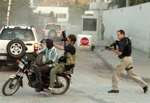 En fotgraf jages av en amerikansk sikkerhetsagent fra USAs ambassade i Port-au-Prince. (Foto: Reuters/Scanpix)