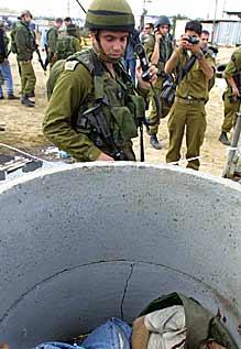 En israelsk soldat ser ned på liket av en av de drepte palestinerne (foto: Nadav Neuhaus/Scanpix)