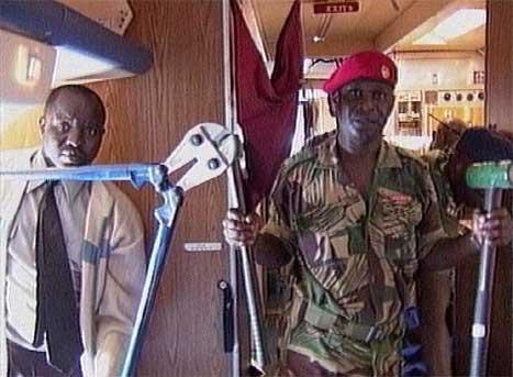 En soldat fra Zimbabwe viser fram noe av utstyret som ble funnet om bord i flyet. (Foto: Reuters/Scanpix)