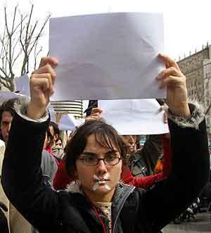 En kvinne i Barcelona holder opp et blankt ark som symboliserer fred, under den stille protesten i Spania i dag. Foto: Albert Gea, Reuters