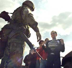 Innbyggere sjekkes av en amerikansk soldat ved et sjekkpunkt mellom Pristina og Mitrovica torsdag. (Foto: Scanpix / Reuters / Hazir Reka)