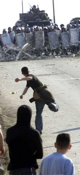 Ein ung albanar kastar stein mot KFOR-soldatar i utkanten av Pristina. (Foto: AP/Scanpix)