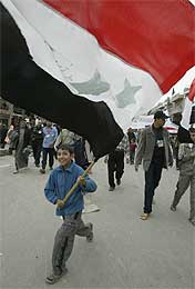 En irakisk gutt løper med sitt lands flagg under en protest mot krigen i Bagdad i går (Scanpix/Reuters)