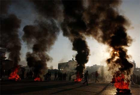 Rasande palestinarar samla seg rundt brennande bildekk i Gaza by. (Foto: AP/Scanpix)