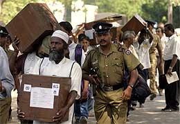 Væpnet politi følger menn med stemmeurner i hovedstaden Colombo (Scanpix/Reuters)