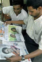 På et hjørne i Colombo studeres morgenavisen med bilder av de to rivalene (Scanpix/AFP)