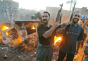 Triumferende militsoldater jublet foran brennende armeikanske kjøretøy i Sadr utenfor Bagdad. (Foto: AFP(