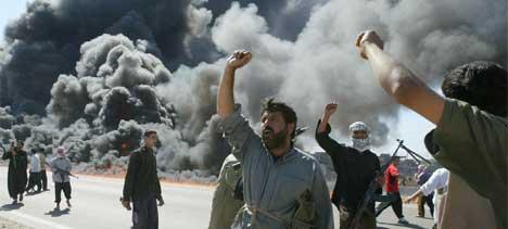 KJEMPER: Irakiske opprørere feirer at de har satt en amerikansk konvoi i brann. Det utkjempes harde kamper i flere deler av Irak i dag. (Foto: AFP PHOTO/Karim Sahib)
