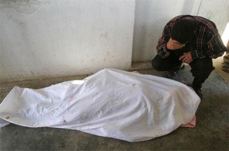 SØRGER OVER SINE DØDE: En mann gråter over kroppen av sin døde tenåringsdatter i Falluja. (Foto: Reuters/Scanpix)