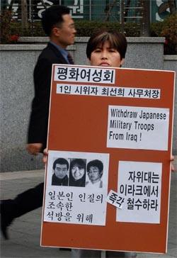 En demonstrant med bilder av de tre gislene ber Japan trekke tilbake sine styrker fra Irak. (Foto: AP/Scanpix)