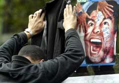 En supporter bøyer seg over et bilde av Maradona utenfor sykehuset i Buenos Aires der han er innlagt. (Foto: Reuters/Scanpix)