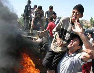 Irakiske ungdommer jubler ved det brennende amerikanske militærkjøretøyet som ble rammet av veibomben. Like etter smalt det, og fire skolebarn ble drept. (Foto: Scanpix / Reuters / Ceerwan Aziz)